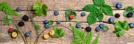Forest berries pattern on rustic wooden background. Banner made of berry fruits and green leaves. Summer concept. Flat lay, long web format, top view Banque d'images