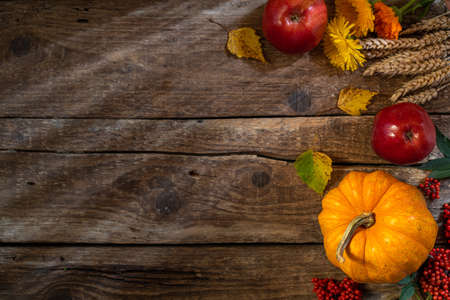 Autumn background for Thanksgiving day. Pumpkin, floral and seasonal fruit decoration on rustic wooden table. Fall background with copy space. Top view