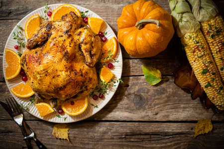 Thanksgiving autumn compositions. Roasted chicken or turkey with citrus and spices, corn for celebrations thanksgiving day on wooden table. Festive table settings for thanksgiving dinner. Top view Foto de archivo