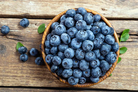 Fresh blueberry in wooden bowl. Juicy and fresh blueberries with green leaves on rustic table. Concept blueberry antioxidant for healthy eating and nutrition. Top view Foto de archivo