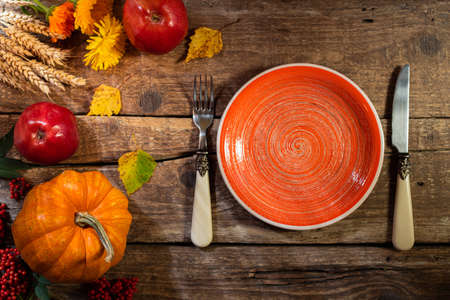 Thanksgiving background. Autumn table setting for Thanksgiving day party or Thanksgiving dinner. Plate, cutlery, pumpkin, floral, fruits and seasonal decoration on rustic wooden table. Copy space Foto de archivo