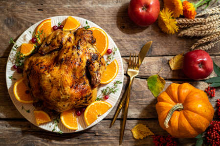 Baked chicken for Thanksgiving Day. Roasted chicken or turkey with citrus and spices for celebrations thanksgiving day on wooden table. Festive table settings for thanksgiving dinner. Top view