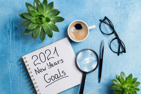 New year goals 2021 on desk. 2021 goals with notebook, coffee cup and eyeglasses on blue background. Resolutions, plan, strategy, action, idea concept. Top view Foto de archivo