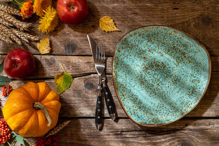 Thanksgiving background. Autumn table setting for Thanksgiving day party or festive dinner. Plate, cutlery, pumpkin, corn, floral, fruits and seasonal decoration on rustic wooden table