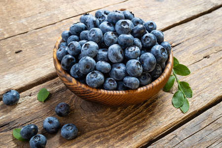 Fresh blueberry in wooden bowl. Juicy and fresh blueberries with green leaves on rustic table. Concept blueberry antioxidant for healthy eating and nutrition Foto de archivo