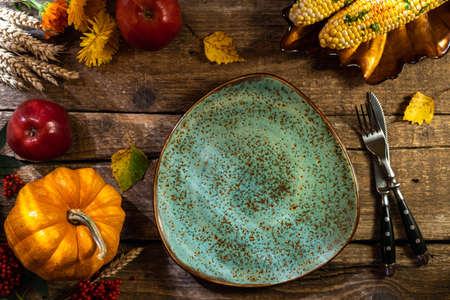Thanksgiving background. Autumn table setting for Thanksgiving day party or Thanksgiving dinner. Plate, cutlery, pumpkin, corn, floral, fruits and seasonal decoration on rustic wooden table