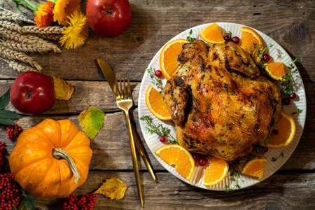 Thanksgiving background. Baked chicken or turkey with citrus and spices for celebrations for Thanksgiving Day on wooden table. Autumn table settings for Thanksgiving dinner. Top view