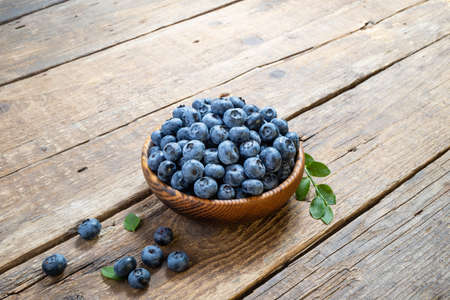 Fresh blueberry in wooden bowl. Juicy and fresh blueberries with green leaves on rustic table. Concept blueberry antioxidant for healthy eating and nutrition. Copy space Foto de archivo