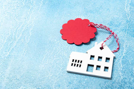House for buy or rent label on winter holidays. Wooden house symbol with tag on blue background. Real estate, rental housing, rent for christmas holidays concept. Copy space