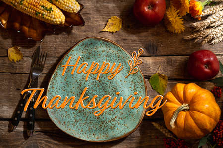 Autumn table setting for Thanksgiving day party or Thanksgiving dinner. Plate, cutlery, pumpkin, floral, fruits and seasonal decoration on rustic wooden table. Top view