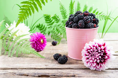 Fresh blackberry on rustic wooden background. Forest berry fruits blackberry and flowers, green leaves. Summer berries healthy food Foto de archivo