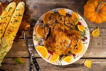 Thanksgiving background. Baked chicken or turkey with citrus and spices for celebrations for Thanksgiving dinner on wooden table. Autumn table settings for Thanksgiving. Top view