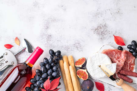 Appetizers on table with italian antipasto snacks and wine. Grape, figs, cheese camembert, bread stick, meat snaks. Antipasti, gourmet, romantic concept. Top view. Copy space