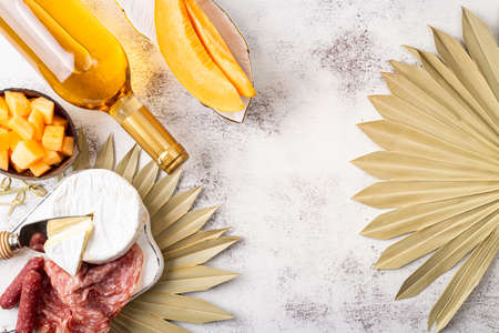 Appetizers on table, antipasto snacks, wine and fruits. Melon cantaloupe, cheese, prosciutto, meat snaks on table decorated palm leaf. Antipasti, gourmet, romantic concept. Copy space Foto de archivo