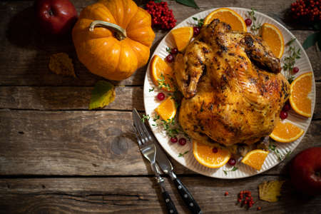 Thanksgiving autumn compositions. Roasted chicken or turkey with citrus and spices for celebrations thanksgiving day on wooden table. Festive table settings for thanksgiving dinner. Top view