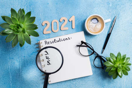 New year resolutions 2021 on desk. 2021 goals with notebook, coffee cup and eyeglasses on wooden background. Goal, plan, strategy, action, idea concept. Copy space
