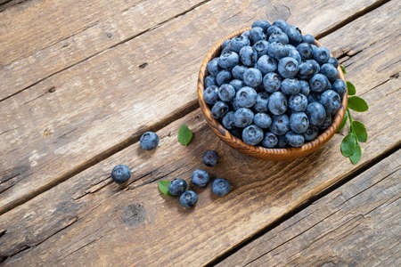 Fresh blueberry in wooden bowl. Juicy and fresh blueberries with green leaves on rustic table. Concept blueberry antioxidant for healthy eating and nutrition. Top view, copy space Foto de archivo