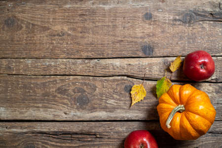 Autumn composition for Thanksgiving day. Pumpkin, fruits apples, autumn leaves on rustic wooden table. Fall seasonal decoration. Autumn background. Top view, copy space