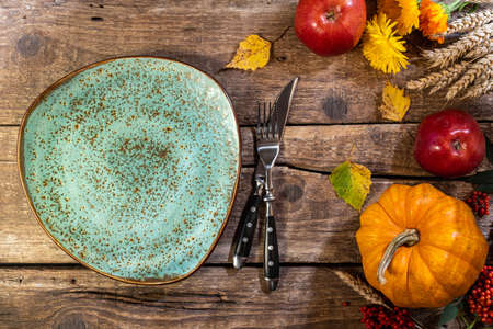 Thanksgiving background. Autumn table setting for Thanksgiving day party or festive dinner. Plate, cutlery, pumpkin, corn, floral, fruits and seasonal decoration on rustic wooden table Foto de archivo