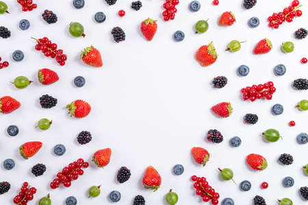 Strawberry, blueberry, blackberry, gooseberry, red currant on white background, top view. Berries pattern, flat lay. Frame made of fresh berry on white background. Creative food concept. Foto de archivo