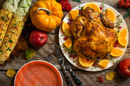 Autumn festive Thanksgiving composition. Baked chicken or turkey with citrus and spices for celebrations for Thanksgiving dinner on wooden table. Table settings for Thanksgiving