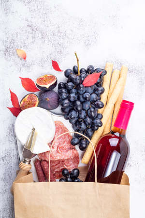 Appetizers in paper bag with italian antipasti snacks and wine. Grape, figs, cheese camembert, bread stick, meat snaks. Antipasto, gourmet, romantic, shopping food supermarket concept. Top view