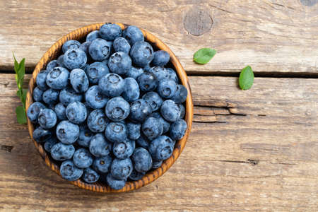 Fresh blueberry in wooden bowl. Juicy and fresh blueberries with green leaves on rustic table. Concept blueberry antioxidant for healthy eating and nutrition. Copy space, top view Foto de archivo