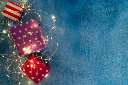 Christmas holidays composition with festive gift boxes and garland illumination on blue. Christmas background with presents in paper package. Copy space