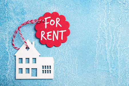 House for rent label on christmas holidays. Wooden house symbol with rent tag on blue background. Real estate, rental housing, rent for winter holidays concept. Top view
