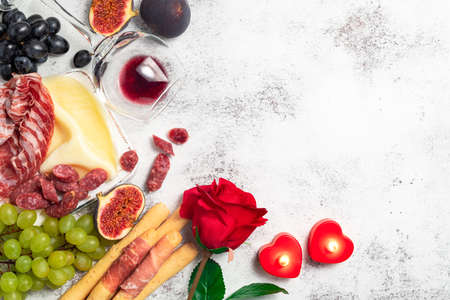 Valentines Day background with appetizers on table italian antipasto snacks and wine. Grape, figs, cheese, bread, prosciutto, meat snaks. Antipasti, gourmet, romantic concept. Copy space