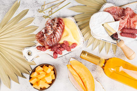 Appetizers on table, antipasto snacks, wine and fruits. Melon cantaloupe, cheese, prosciutto, meat snaks on table decorated palm leaf. Antipasti, gourmet, romantic concept. Top view Foto de archivo