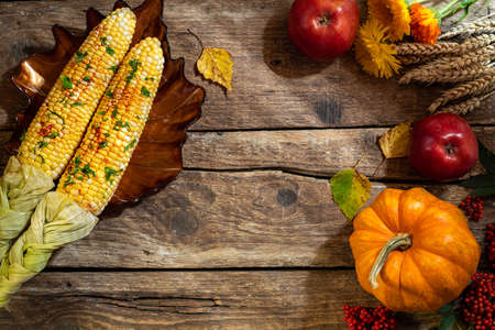 Autumn background for Thanksgiving. Autumn table setting for Thanksgiving dinner. Plate with corn, pumpkin, floral, fruits and seasonal decorations on rustic wooden table. Copy space