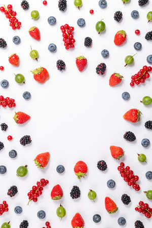 Frame of berry background. Strawberry, blueberry, blackberry, gooseberry, red currant on white background, top view. Berries pattern, flat lay. Creative of healthy food concept