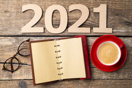 New year resolutions 2021 on desk. 2021 resolutions with open notebook, coffee cup, eyeglasses on wooden background. Goals, plan, strategy, action, idea concept. New Year 2021 template with copy space