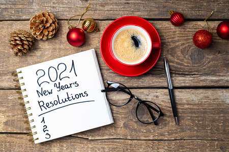New year 2021 resolutions on desk. 2021 goals with notebook, coffee cup, eyeglasses, Christmas ornaments on wooden background. Goals, plan, strategy, action, idea concept. 2021 template, copy space Foto de archivo