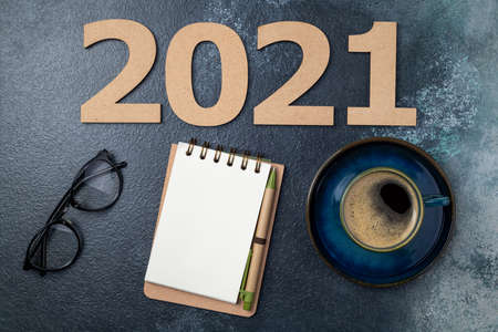New year 2021 and notebook on desk. 2021 template with open notebook, coffee cup, eyeglasses on blue background. Goals, planning, strategy, resolutions, business concept. Copy space
