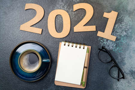New year 2021 and notebook on desk. 2021 template with open notebook, coffee cup, eyeglasses on blue background. Goals, plan, strategy, resolutions, idea concept. Copy space