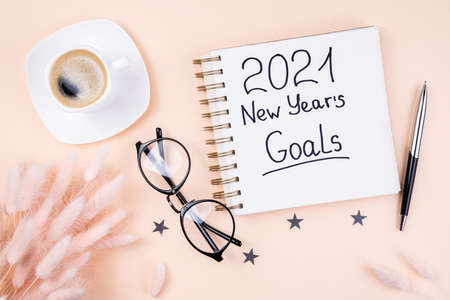 New year 2021 goals on desk. 2021 goals with open notebook, coffee cup, eyeglasses, flowers on pastel background. Resolutions, goals, plan, strategy, feminine, idea concept. New Year 2021 template, copy space