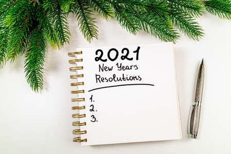 New year resolutions 2021 on desk. 2021 goals with open notebook, coffee cup, christmas tree on white background. Goals, plan, strategy, action, idea concept. New Year 2021 template