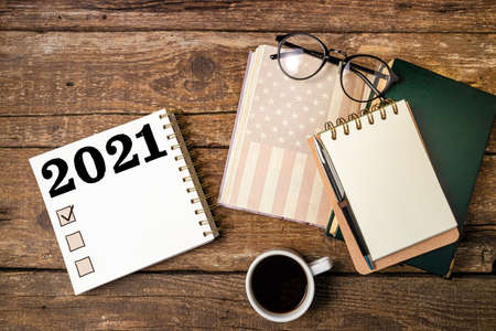 New year resolutions 2021 list. Office desk table with notebooks, coffee cup, american flag. Goal, plan, ideas, business, motivation, checklist concept Foto de archivo