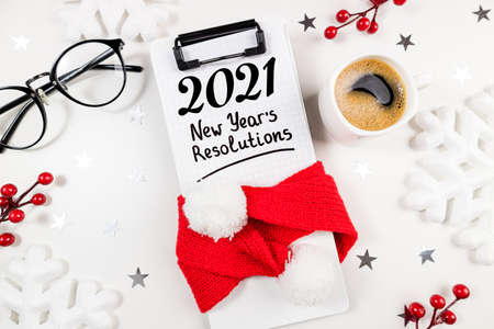 New year resolutions 2021 on desk. 2021 resolutions with open notebook, coffee cup, Christmas decorations on white table. Resolutions, plan, goals, action, idea concept. New Year 2021 template, copy space Foto de archivo