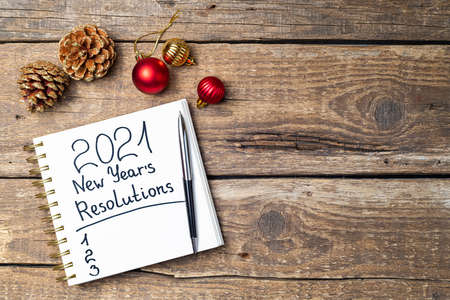 New year resolutions 2021 on desk. 2021 resolutions with open notebook, Christmas ornaments on wooden background. Goals, plan, strategy, action, idea concept. New Year 2021 template with copy space