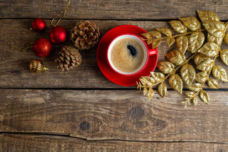 Christmas toys, red cup of coffee, decorations on wooden background. Christmas composition with aroma coffee cup. Holiday, Christmas, New Year concept. Copy space