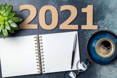 New year 2021 and notebook on desk. 2021 template with open notebook, coffee cup, eyeglasses, plant succulent on blue background. Goals, plan, strategy, resolutions, business concept. Copy space