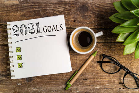New year goals 2021 on desk. 2021 goals list with notebook, coffee cup, plant on wooden table. Resolutions, plan, goals, checklist, idea concept. New Year 2021 template, copy space