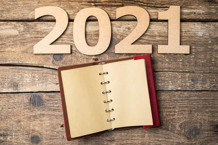 New year resolutions 2021 on desk. 2021 resolutions with open notebook on wooden background. Goals, plan, strategy, action, idea concept. New Year 2021 template with copy space Foto de archivo