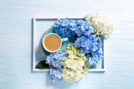 Bouquet of beautiful hydrangea and coffee cup on blue wooden background. Blue flowers hortensia. Abstract floral composition with blue and white flowers. Copy space Foto de archivo