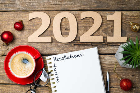 New year 2021 resolutions on desk. 2021 goals with notebook, coffee cup, eyeglasses, Christmas decorations on wooden background. Goals, plan, strategy, action, idea concept. New Year 2021 template