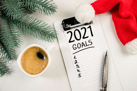 New year goals 2020 on desk. 2020 resolutions on workplace with coffee cup, notebook, pen, christmas tree and santa hat. Goal, plan, strategy, change, idea concept. Top view