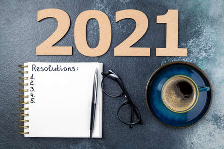 New year resolutions 2021 on desk. 2021 resolutions with open notebook, coffee cup, eyeglasses on blue background. Resolutions, goals, planning, strategy, business concept. Copy space